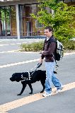 Guide Dog trialist walking and using hand controller to find signal from a base station.